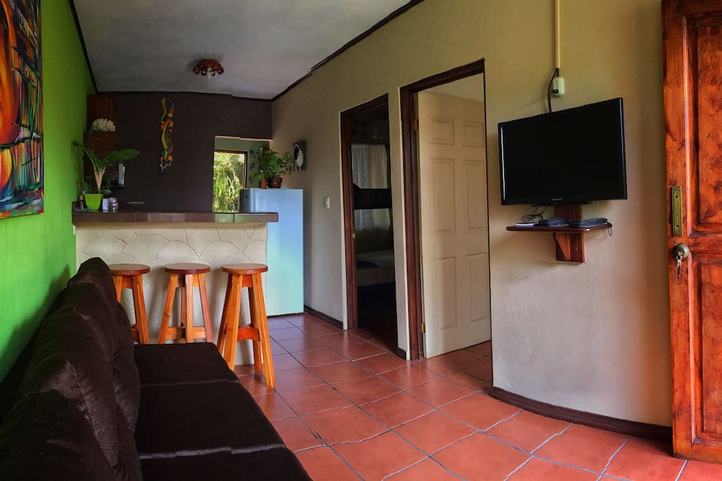 """Spacious fully furnished kitchen (appliances and cooking ware) with bar top connected to the cozy living room equipped with a comfortable couch, 32"""" plasma TV and cable. Wifi available throughout the apartment."""