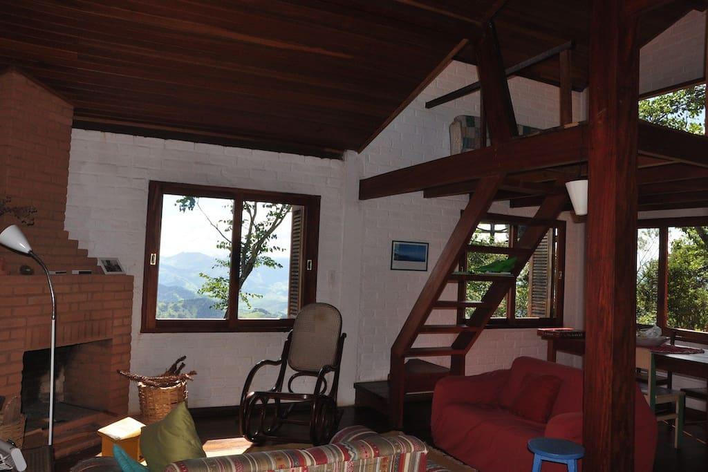 Sala com 2 sofás, 2 poltronas diante da lareira