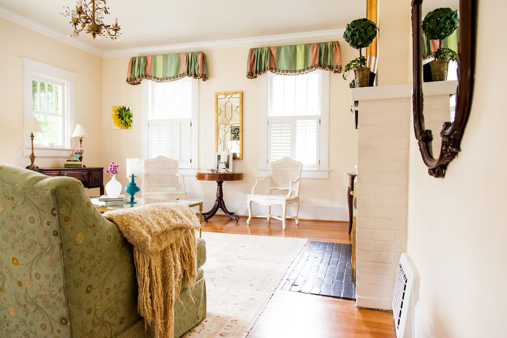 The formal living room is professionally decorated with silk draperies and fine upholstery.