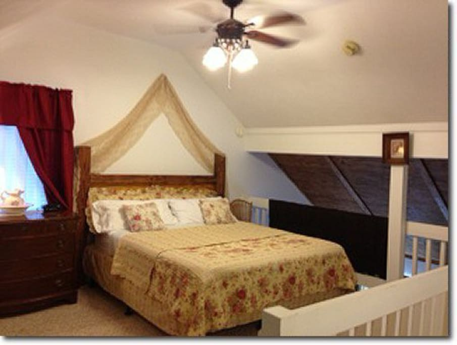 King size bed in large open loft bedroom, vaulted ceilings, ceiling fan, dresser, closet & rocking chair.