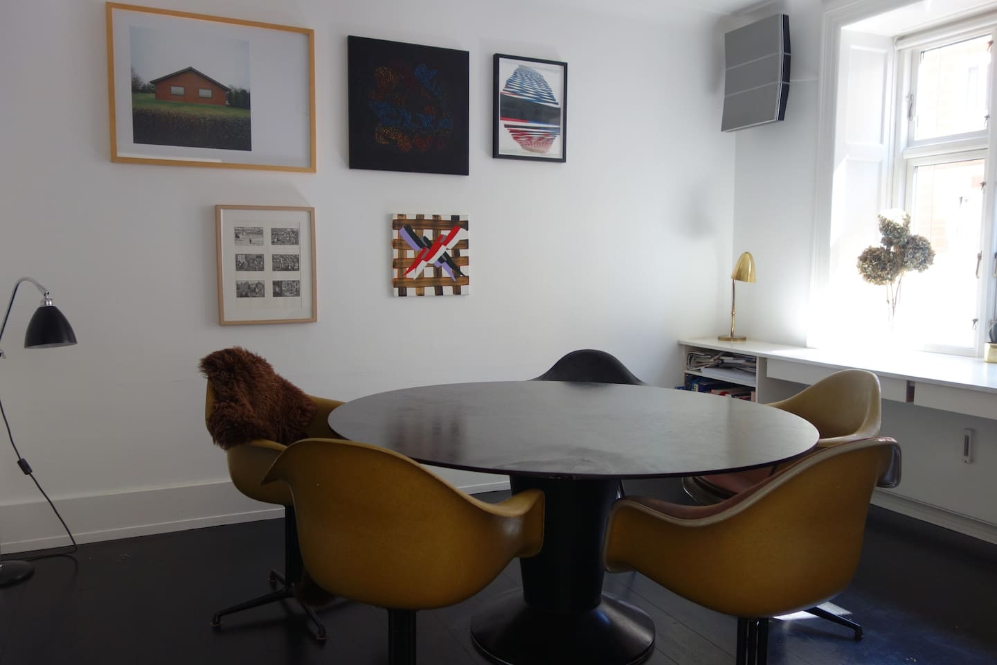 Dining room with large table, eames chairs, great stereo and contemporary danish art.