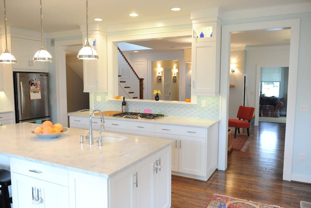The contemporary kitchen has Carrera marble countertops and stainless steel appliances in the kitchen.