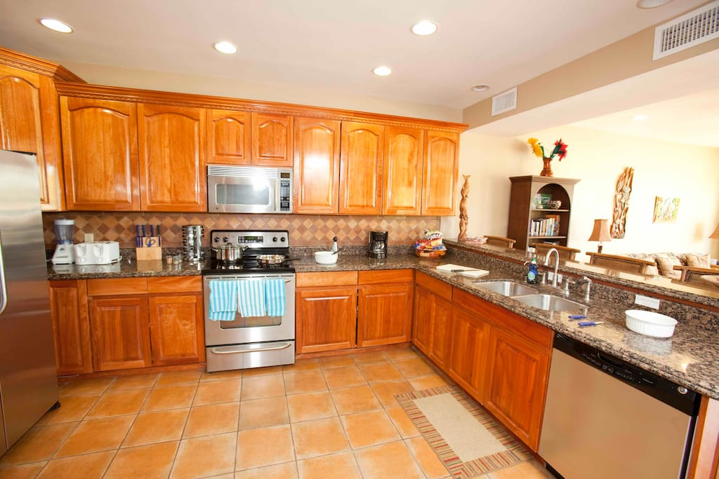 Gourmet kitchen with stainless appliances, granite counters, local hardwood cabinets and tile floors
