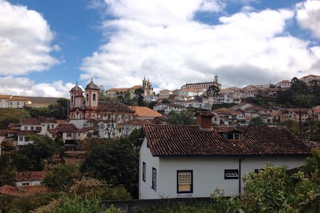 Our lodging house has 4  en suite bedrooms, which accommodate 2 people each, with comfort and privacy. Its view contemplates a beautiful landscape of the city. Its location is central and dispenses the use of car. It's close to Chico Rei's Mine and Nossa Senhora da Conceição Church. It has equipped kitchen and Wi-Fi.