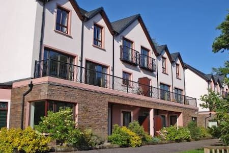 "4-room terraced house on 2 levels, comfortable and tasteful furnishings: living/dining room with open-hearth fireplace, cable TV, CD-player and DVD. Exit to the balcony, to the patio. Open kitchen (4 hot plates, oven, dishwasher, microwave). Sep. WC. Upper floor: 1 room with 1 double bed, bath/shower/WC and whirlpool. 1 room with 2 beds and bath/shower/WC. 1 room with 1 bed and shower/WC. Floor heating. Balcony, patio. Terrace furniture. Beautiful view of the river. Facilities: washing machine, dryer, iron, hair dryer. Please note: TV only EN. The fireplace is electric. Some houses have patios, others have balconies with terrace furniture.Comfortable holiday development ""Grove Lodge"". 500 m from the centre of Killorglin, in a quiet, sunny position, 100 m from the river. Parking at the house. Shop, grocery, restaurant, café 500 m. Golf course (18 hole) 4 km. Please note: baby equipment on request. This new development is set on the banks of the River Laune, just five minutes stroll from Killorglin Town Centre and enjoys panoramic view of the MacGillycuddy Reeks (Ireland's highest mountain range).