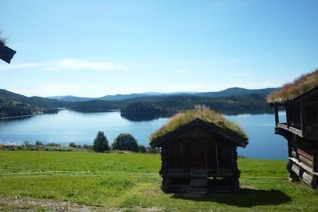 Lita hytte i solfylt gårdstun. - Blockhütte